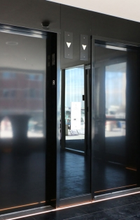 "Description: Elevator lobby designed with 1/4"" back-painted glass creates a sophisticated and elegant wall treatment."