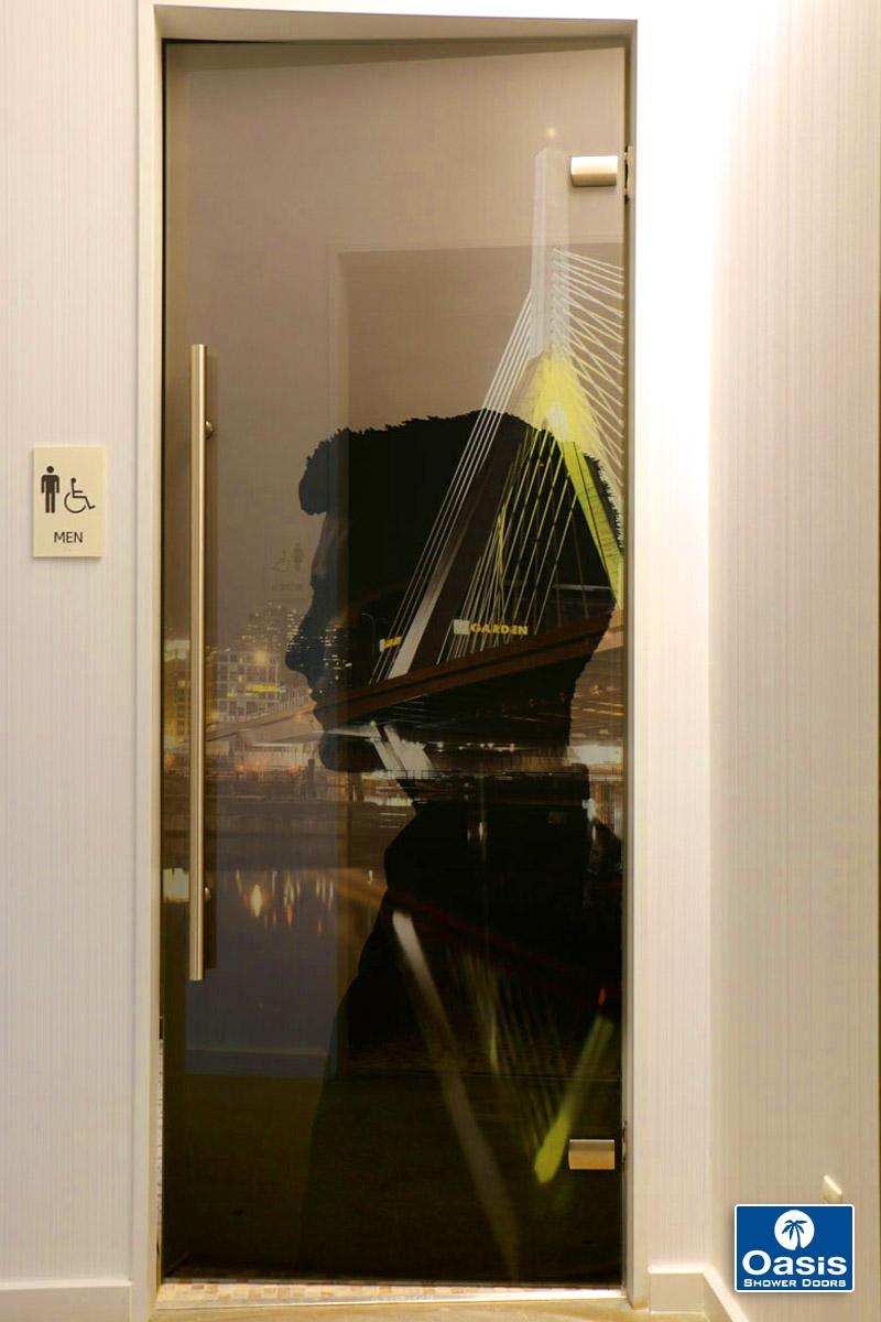 "Description: 1/2"" low-iron, imaged glass entrance doors for ground floor public restrooms."