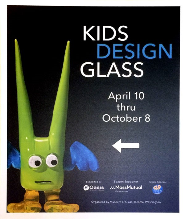 A small glass creature with blue wings, big yellow feet, and green horns, designed by a kid and created by a professional glass artist.